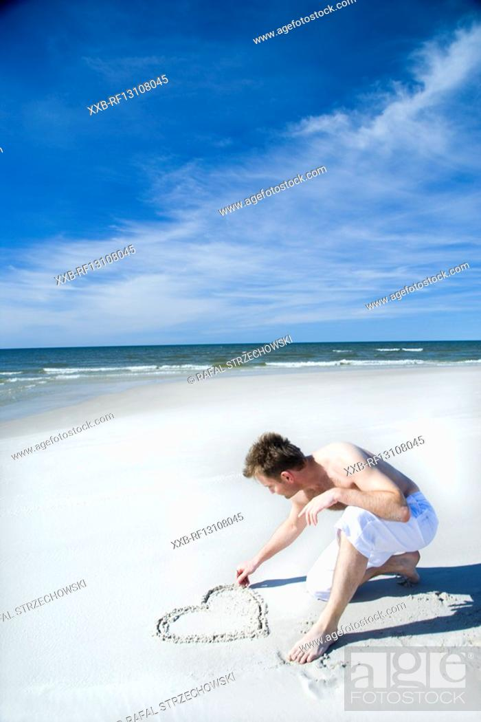 Stock Photo: man drawing heart on sand.