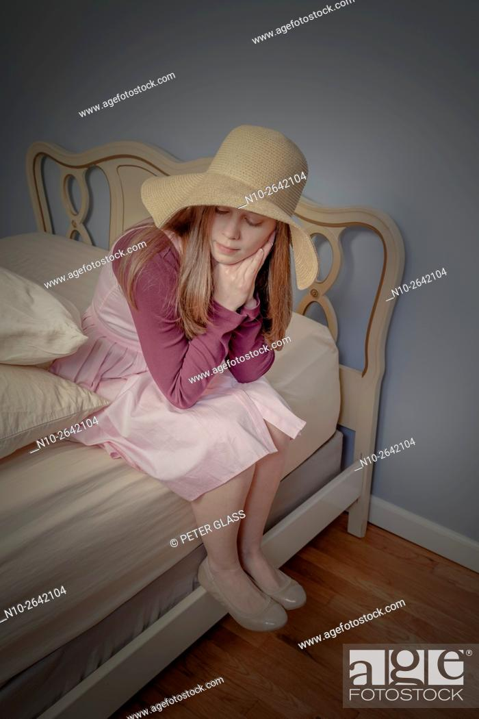 Stock Photo: Young woman, wearing a hat, sitting on a bed.