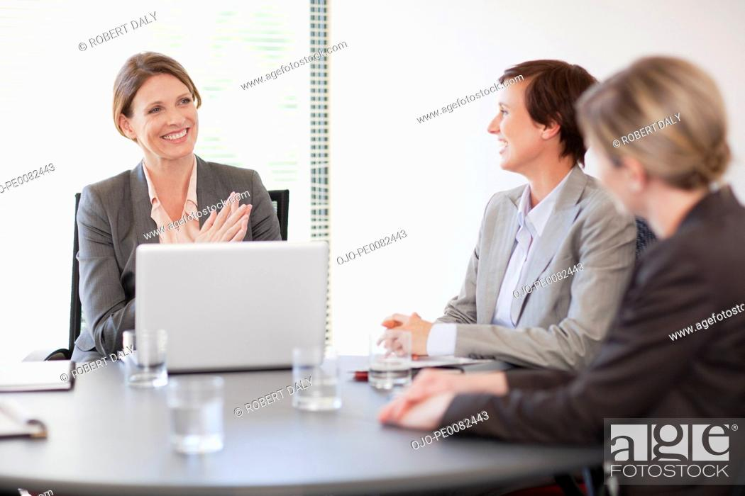 Stock Photo: Smiling businesswomen with laptop meeting in conference room.