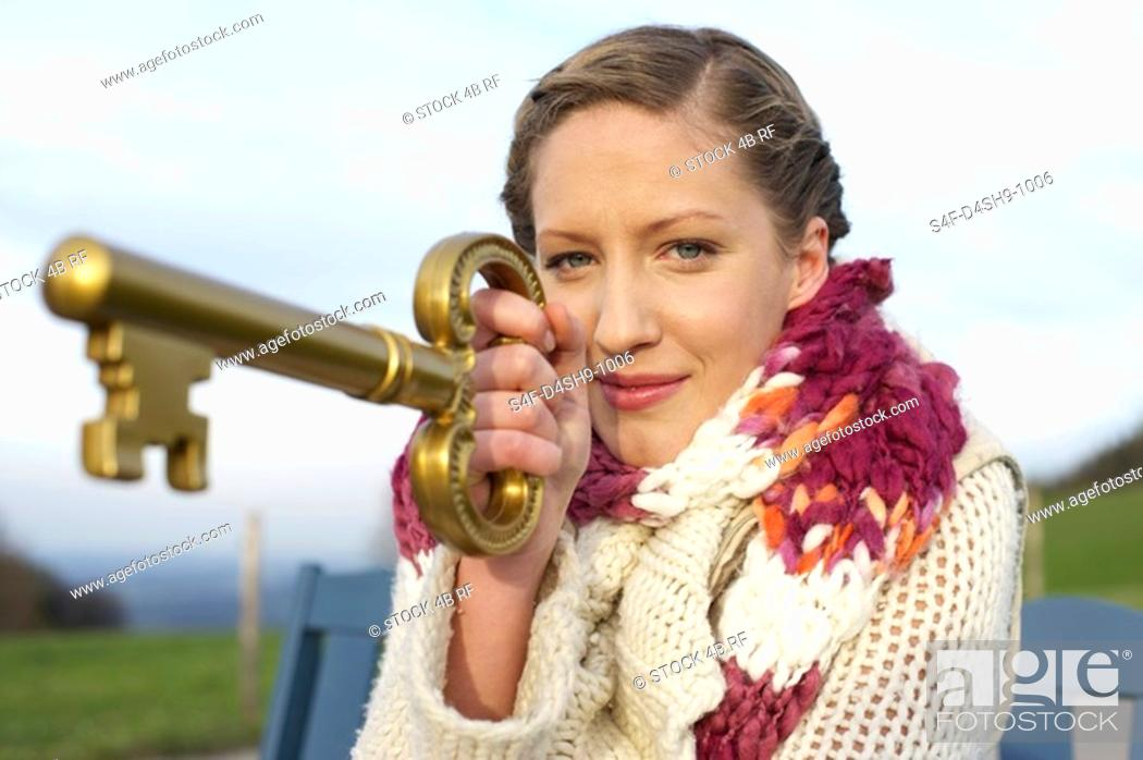 Stock Photo: Young woman with scarf and cardigan holding a huge key, close-up.