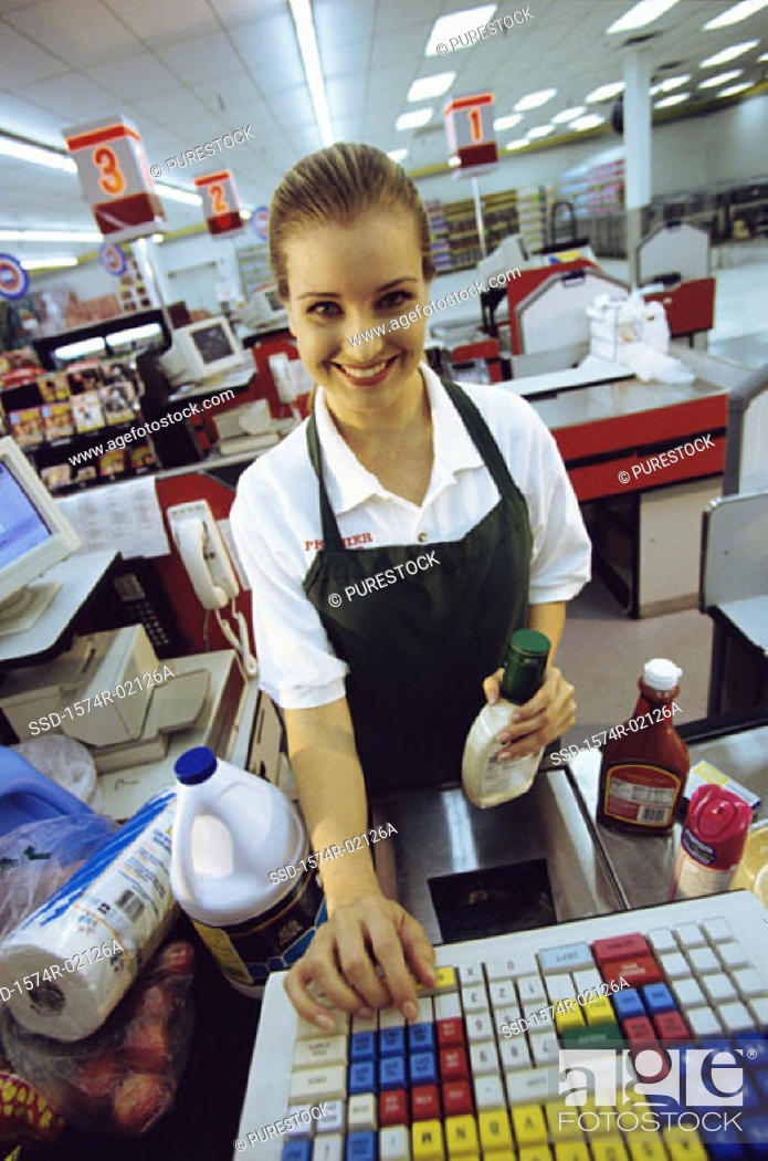 Stock Photo: Portrait of a female sales clerk working on a cash register at a supermarket checkout counter.