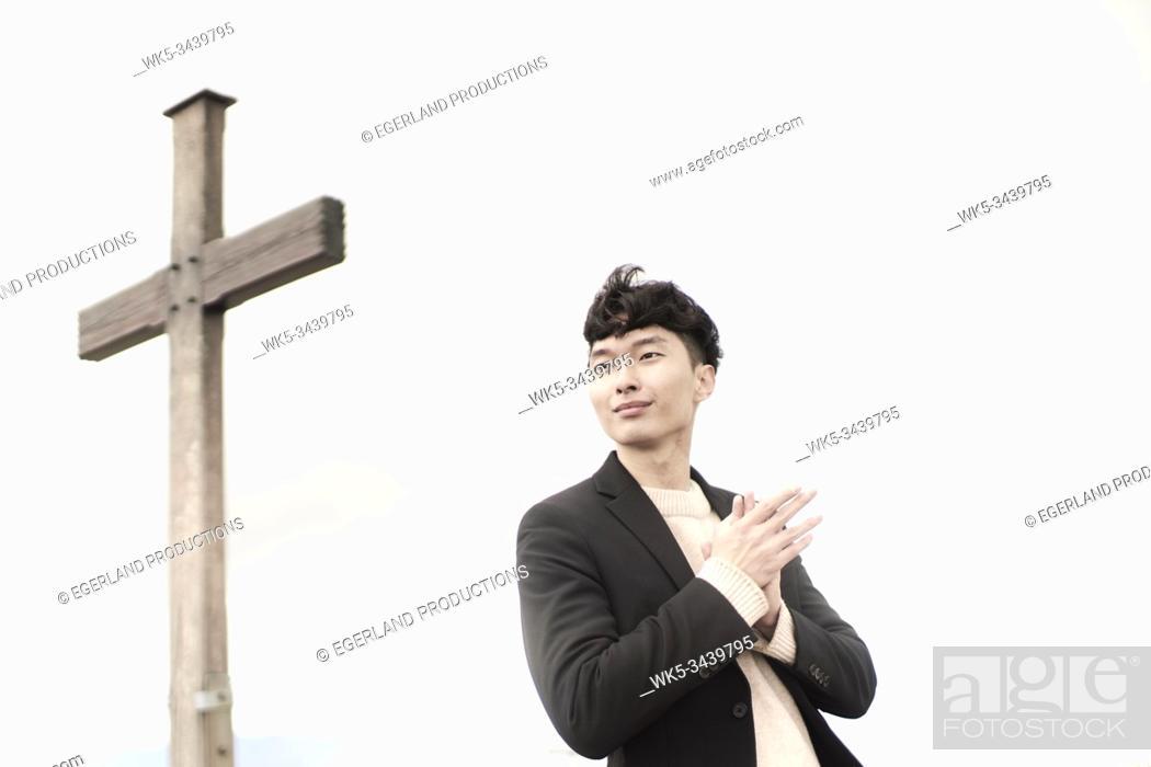 Stock Photo: Korean man at summit cross.