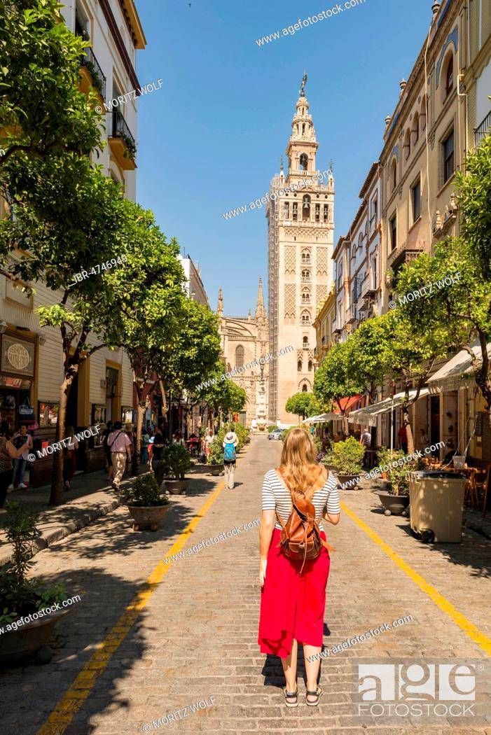 Stock Photo: Woman with red dress on street, overlooking La Giralda, belfry of Seville Cathedral, Catedral de Santa Maria de la Sede, Seville, Andalusia, Spain.