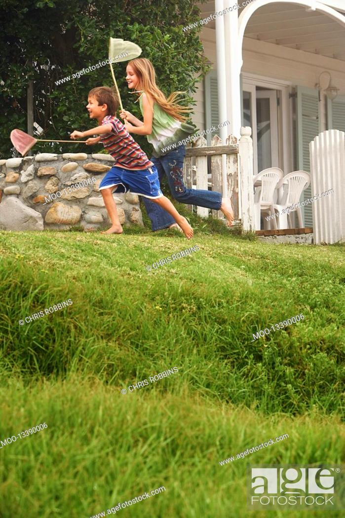 Stock Photo: Brother and sister 5-6 10-12 holding fishing nets running in front of house.
