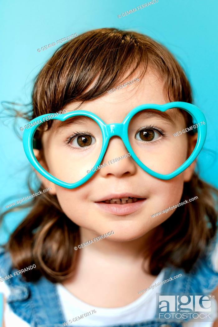 Stock Photo: Portrait of cute little girl with heart shaped glasses on blue background.