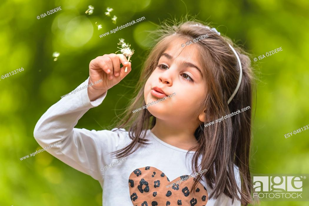 Photo de stock: Outdoor portrait of adorable four years old cute little girl blowing a dandelion wild flower at meadow in a sunny day.