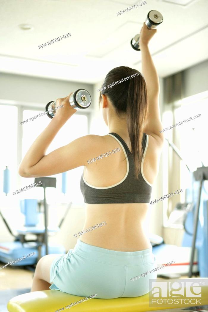 Stock Photo: A young woman lifts dumbbells with both hands as she works out in the gym.