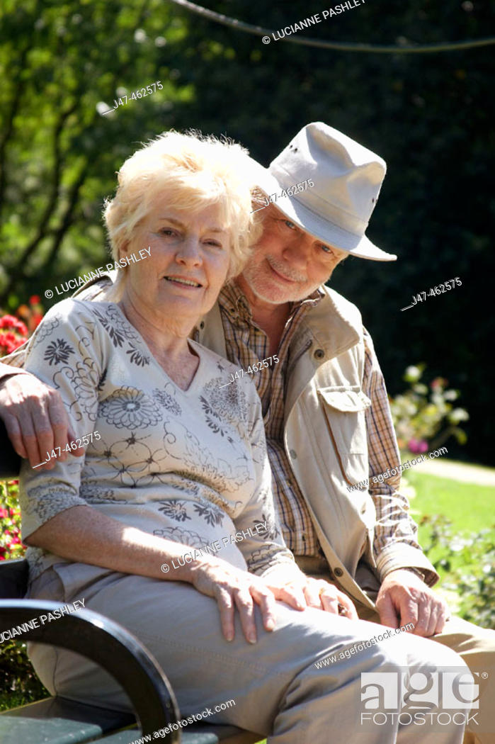Stock Photo: 69, and 70 year old couple sitting on a park bench, hes got his arm round her, smiling into camera.
