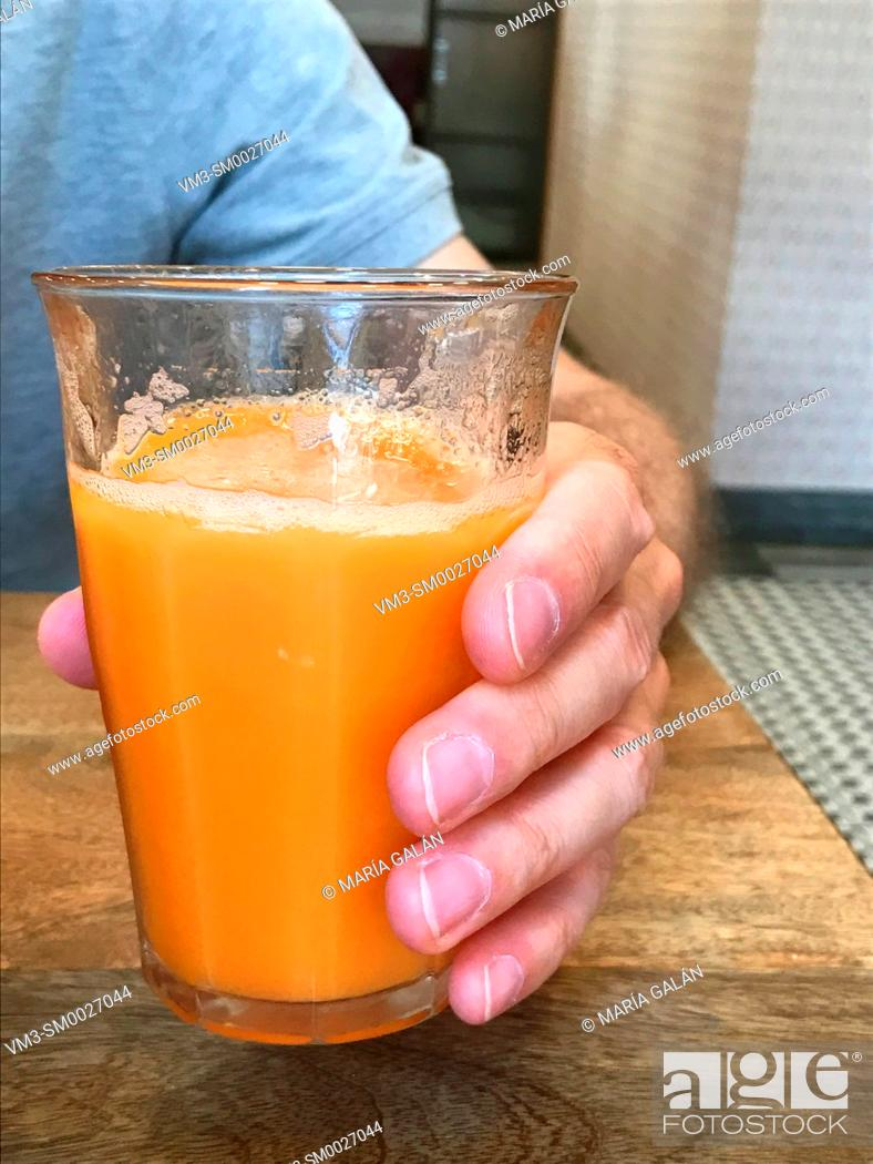 Stock Photo: Man's hand holding a glass of fruit juice. Close view.