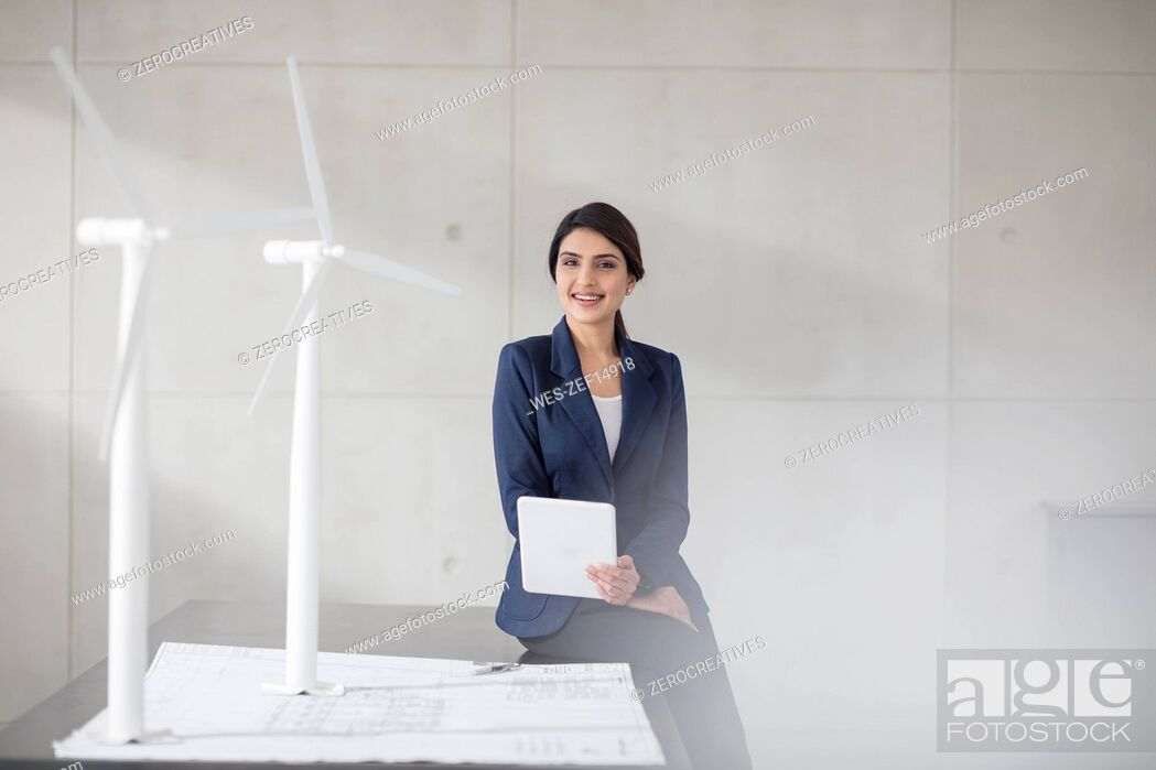 Stock Photo: Portrait of smiling young woman with blueprint, wind turbine models and tablet in office.