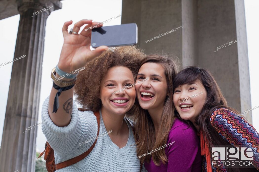 Stock Photo: Low angle view of smiling young female friends taking selfie.
