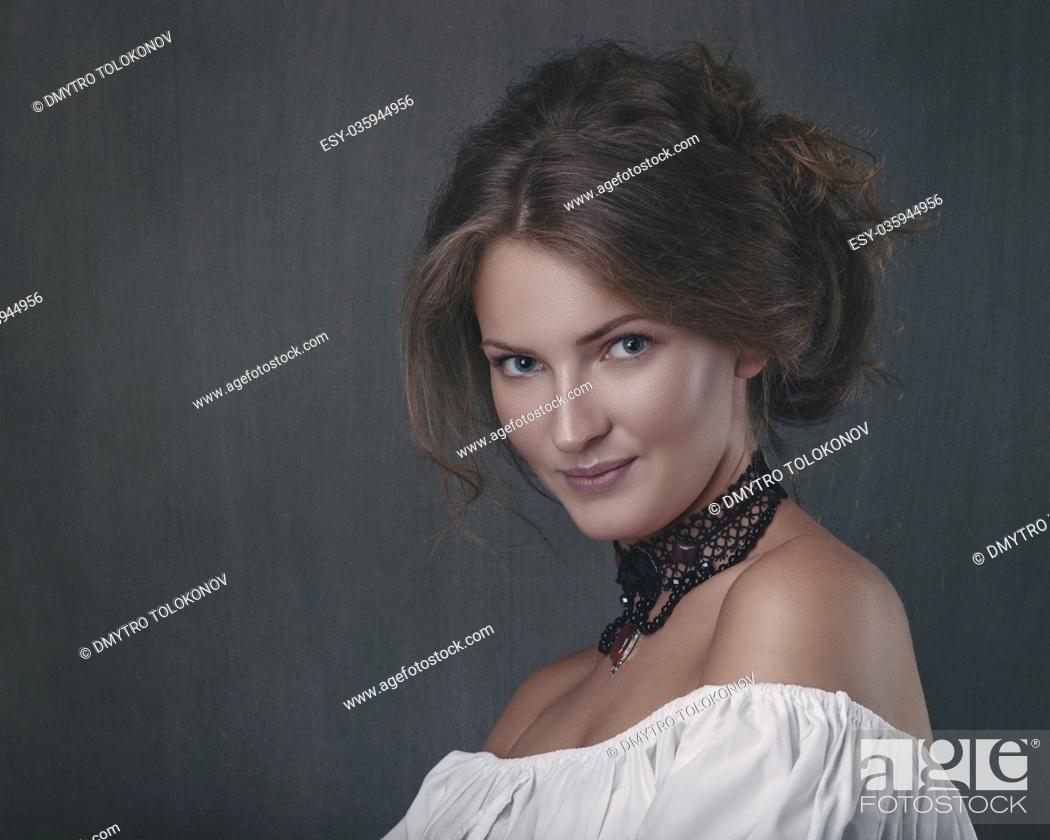 Stock Photo: Grungy female portrait. Retro styled classic dramatic light.