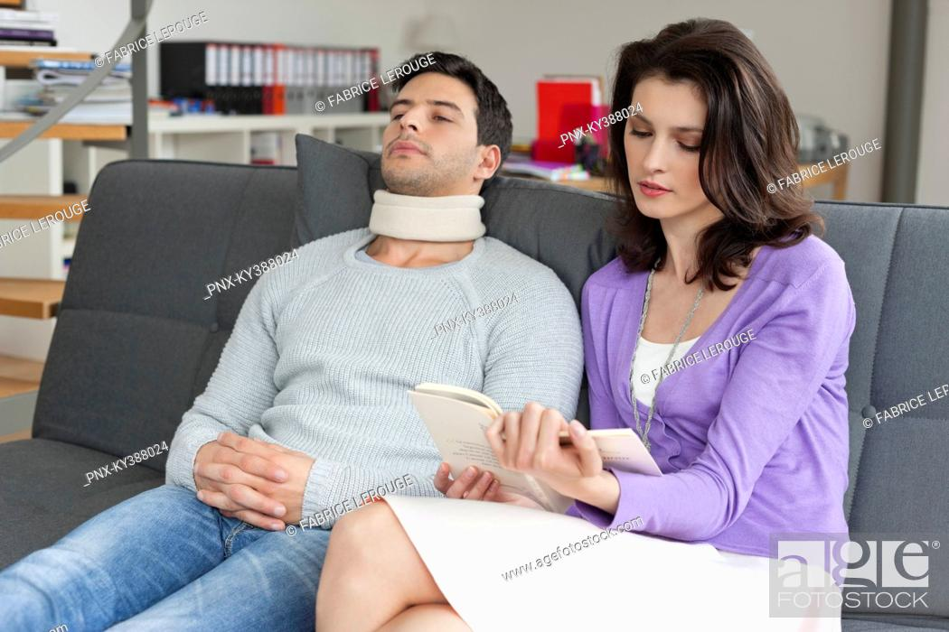 Stock Photo: Woman reading a book for her husband suffering from neckache.