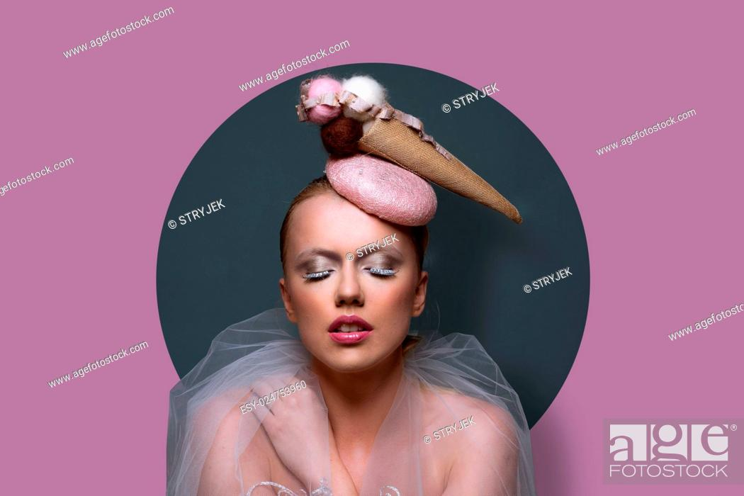 Stock Photo: Fine art portrait of a gorgeous woman in fascinator hat in the shape of an ice cream cone with creative makeup and filmy gauze around her shoulders over a.