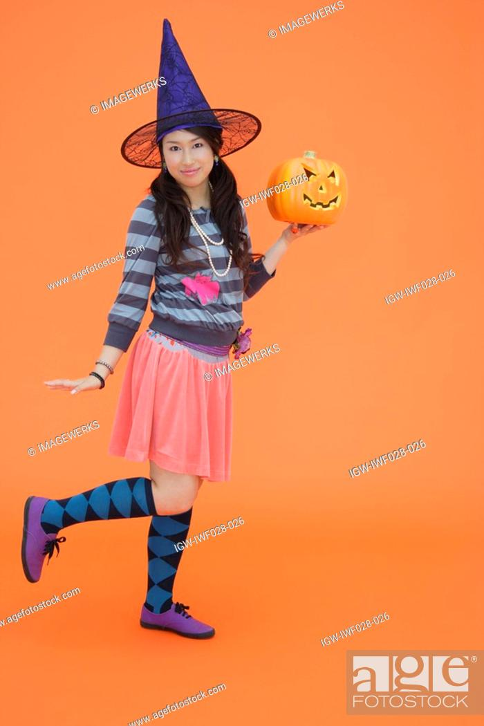 Stock Photo: View of a teenage girl holding jack-o-lantern.