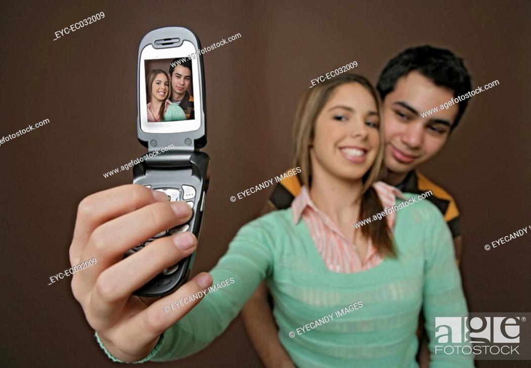 Stock Photo: View of a couple clicking a photograph through their cellphone.