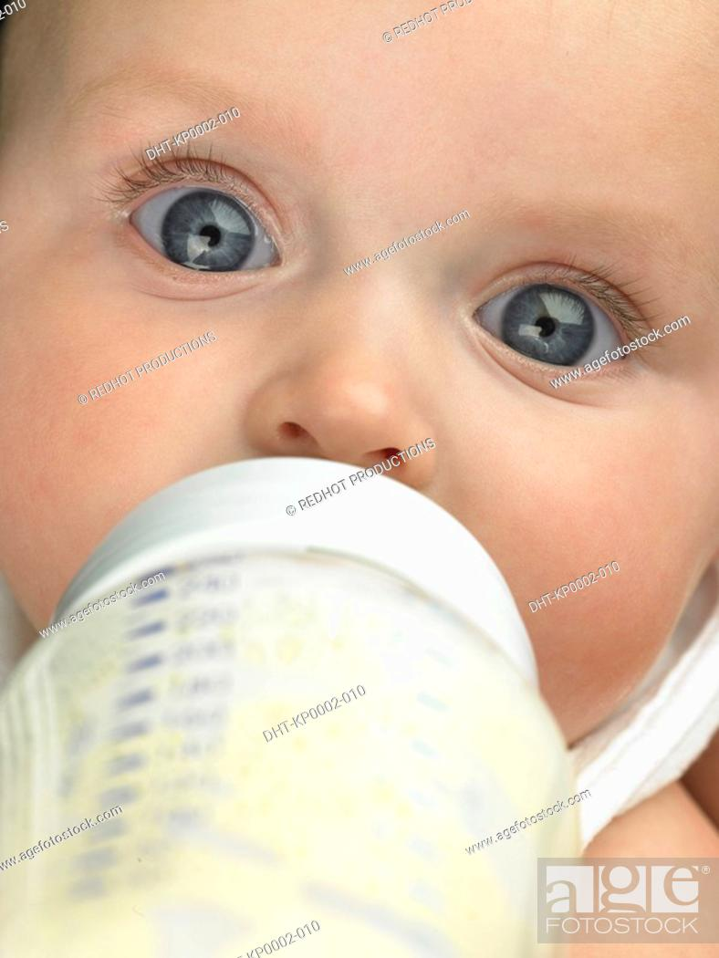 Stock Photo: Baby's face close up with baby bottle.