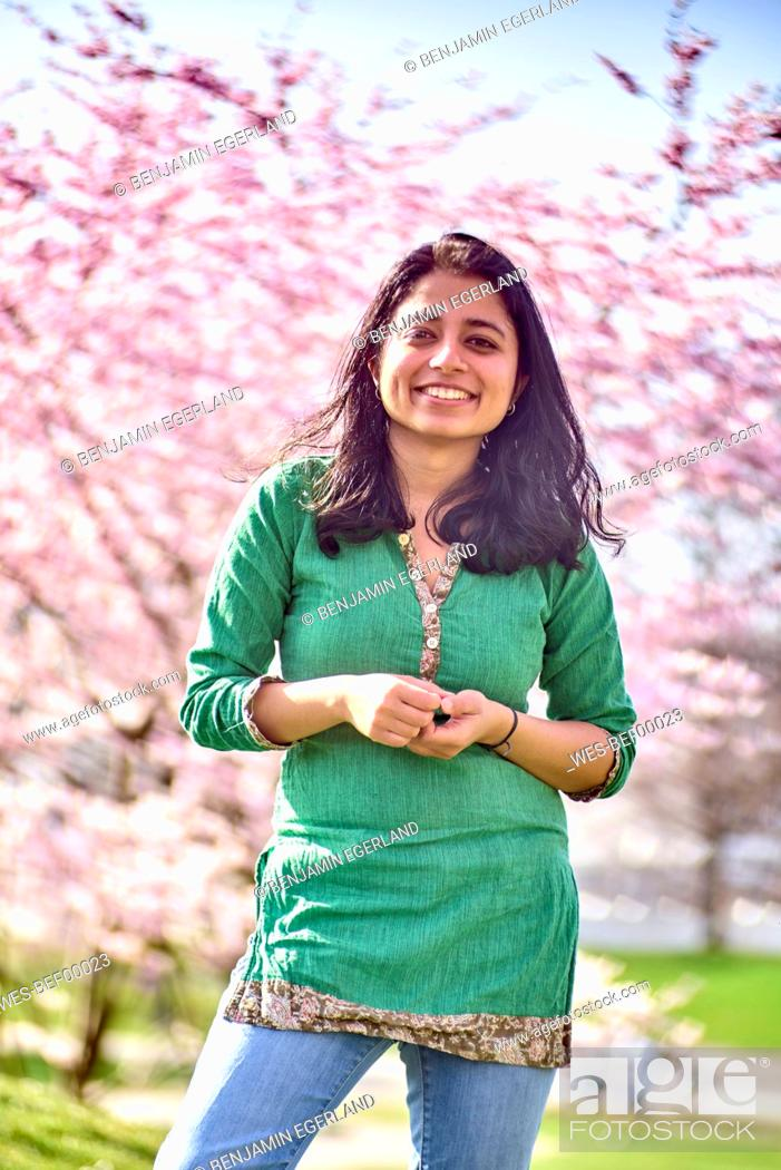 Stock Photo: Portrait of happy young woman in a park at cherry blossom tree.