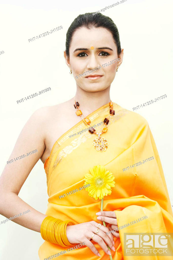 Stock Photo: Portrait of a young woman holding a flower.