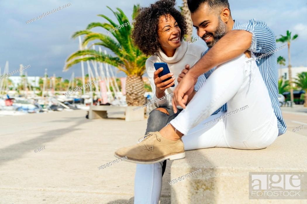 Photo de stock: Spain, Barcelona, happy couple with cell phone at the marina.