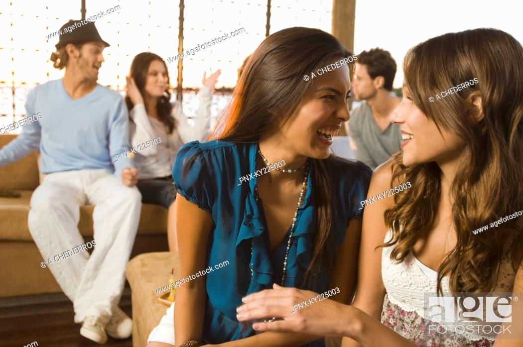 Stock Photo: Two women smiling with their friends in the background.
