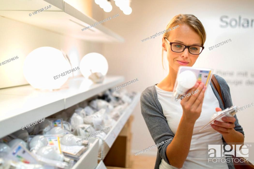 Imagen: Energy efficient lighting choice: Pretty, young woman holding and choosing a LED diode light bulb for her lamp in DIY department store.