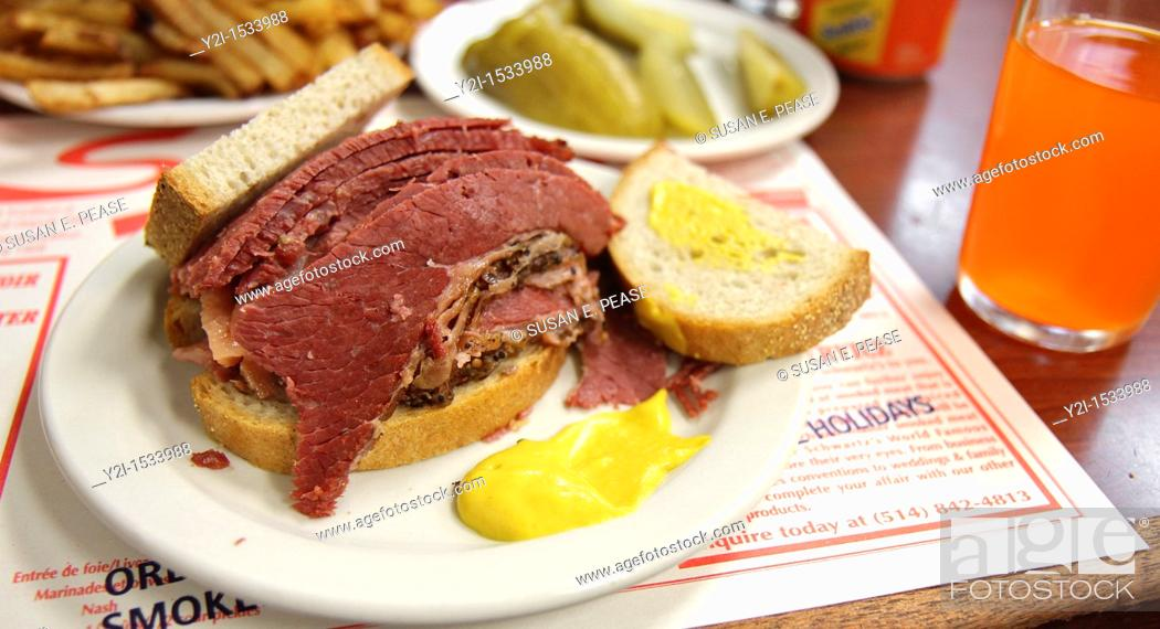 Stock Photo: A smoked meat sandwich and pickles at Schwartz's in Montreal, a Hebrew Delicatessan that opened in 1928  Montreal, Quebec, Canada.