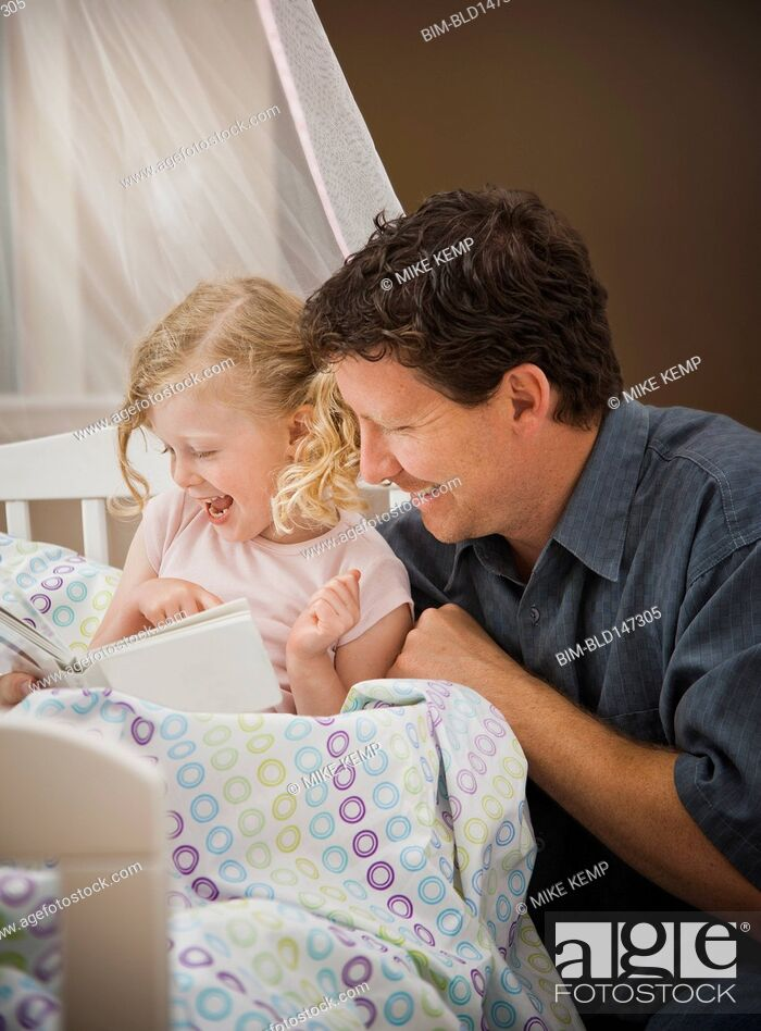 Stock Photo: Caucasian father reading book to daughter in bed.