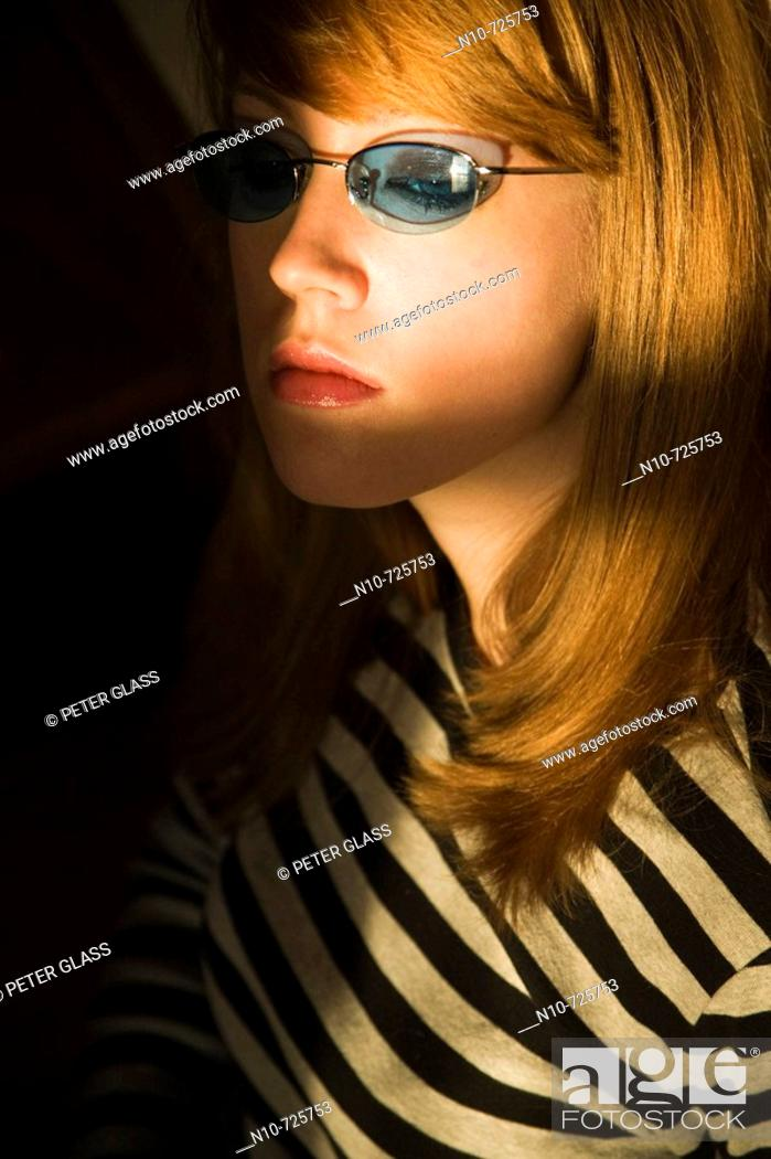 Stock Photo: Young blond woman, wearing sunglasses, being lit by sunlight.