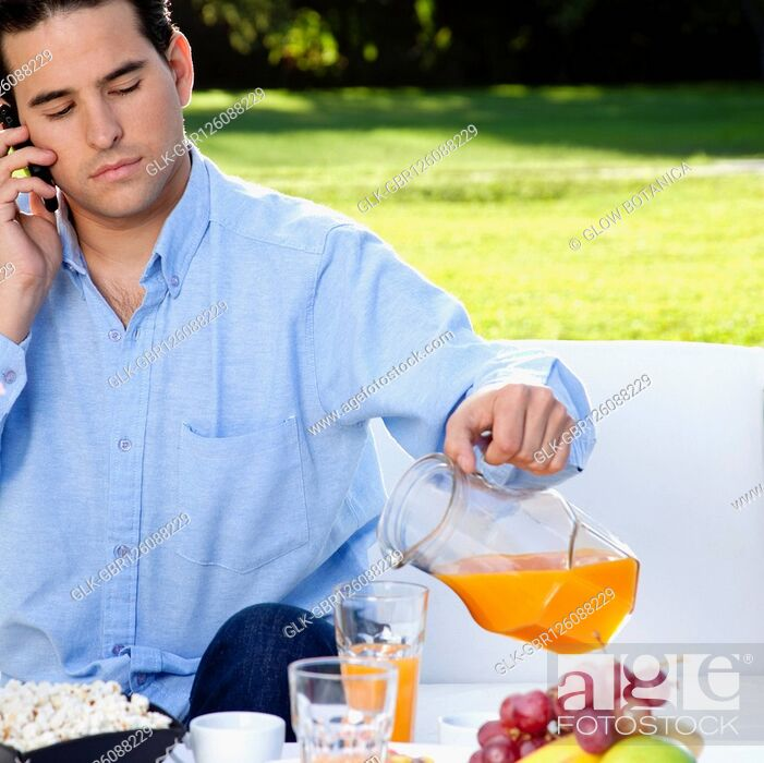 Stock Photo: Man talking on a mobile phone while having breakfast.