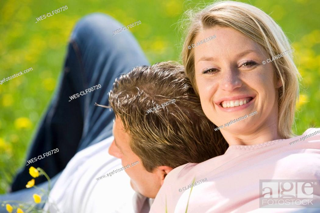 Stock Photo: Germany, Bavaria, Munich, Young couple sitting in meadow, portrait.