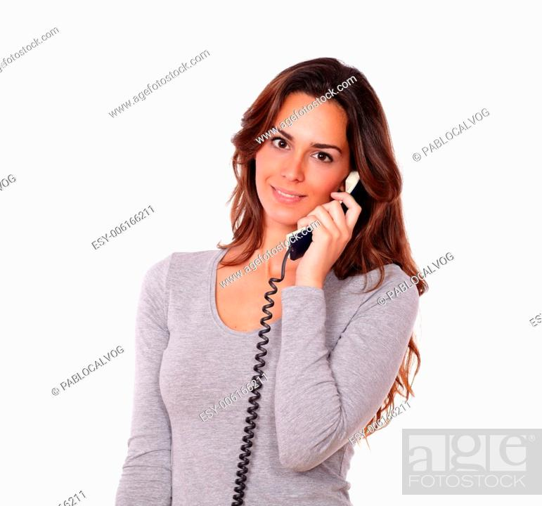Stock Photo: Portrait of a stylish young female talking on phone while standing in white background.