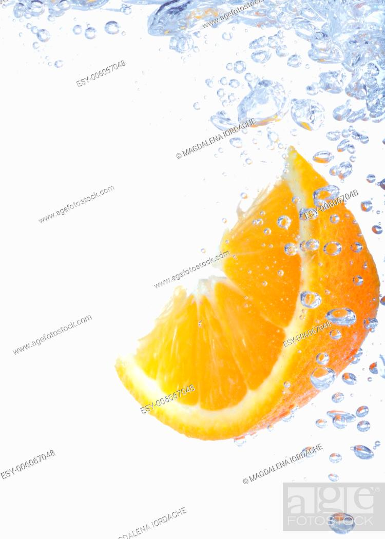 Stock Photo: close-up of lemon slice in clear water with bubbles.