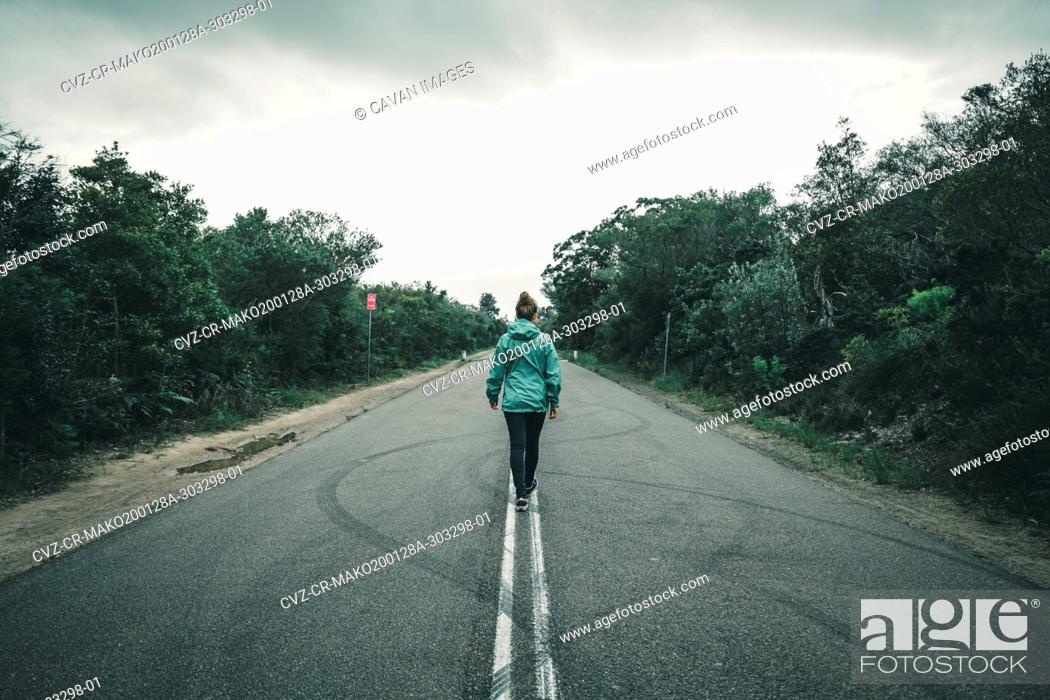 Imagen: Rear View of young woman walking on highway.