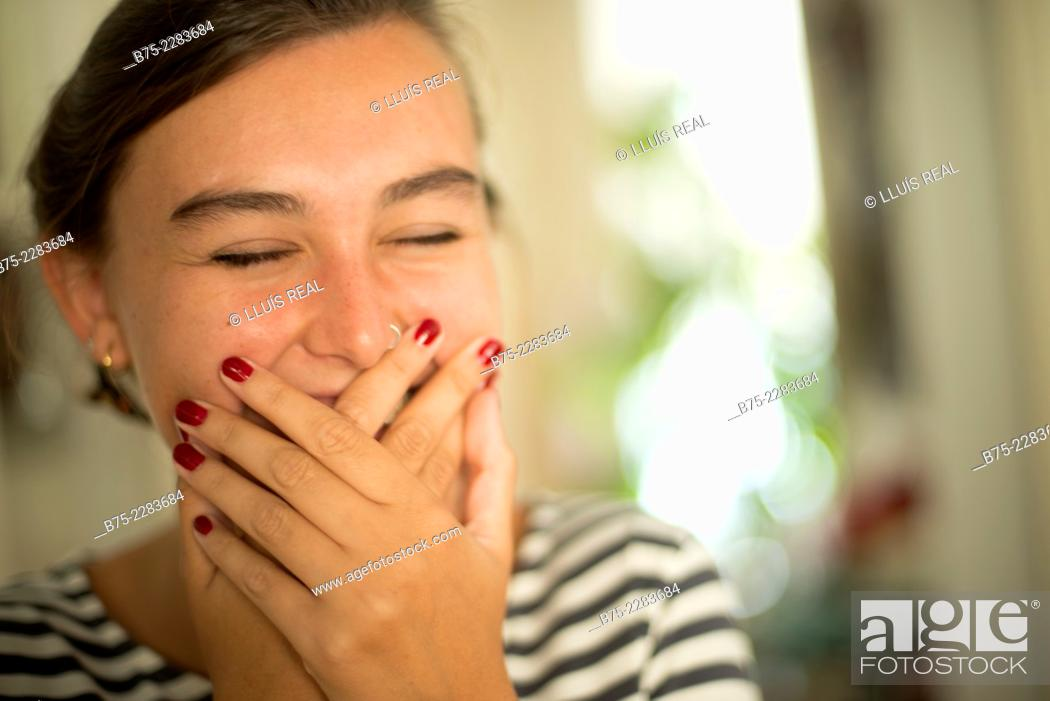 Photo de stock: Portrait of young woman covering her mouth with hand, smiling, happy and joy.