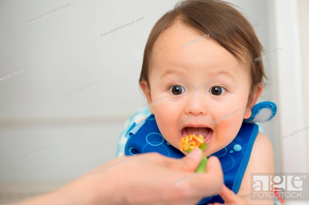 Stock Photo: Hand of mother feeding baby food to open mouthed son in kitchen.