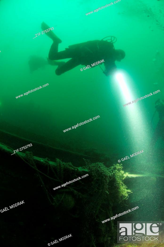 Stock Photo: Divers exploring a wreck with their lamp in Brittany, France.