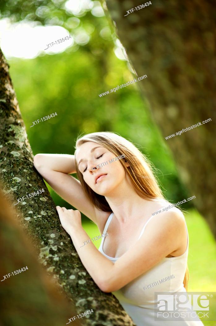 Stock Photo: a young caucasian woman eyes closed, outdoors in a woodland glade, uk.