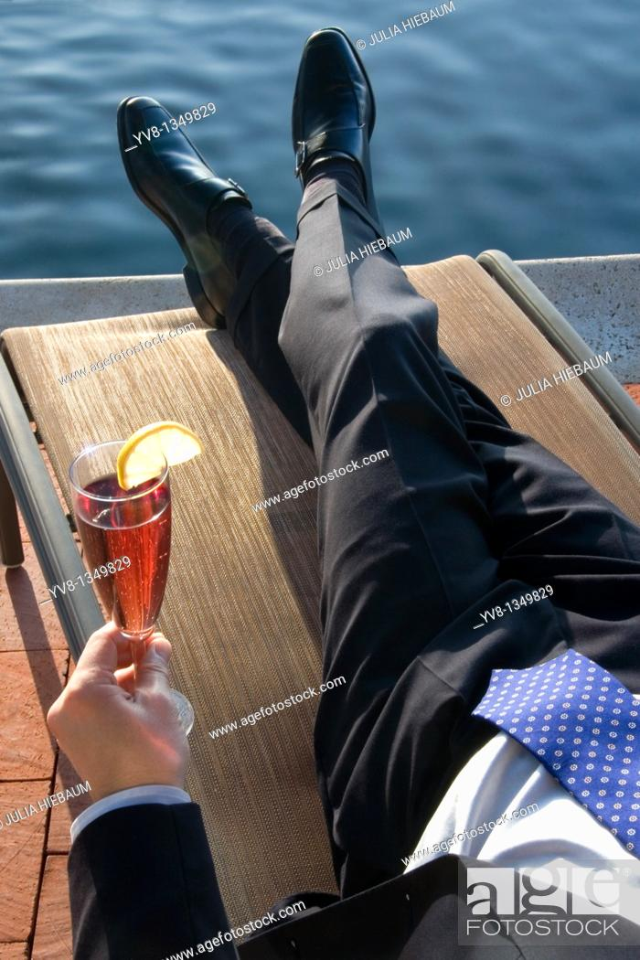 Stock Photo: Executive relaxing by the pool.