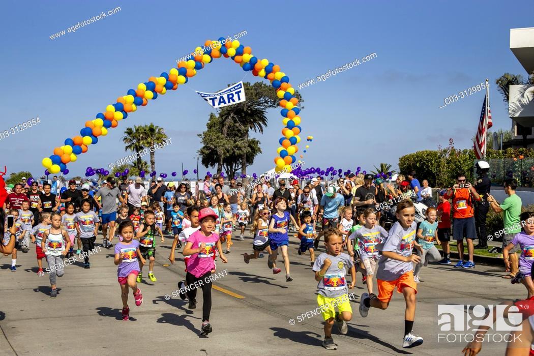 "Stock Photo: Children begin a """"Kid's Dolphin Dash"""" foot race under an arch of balloons in Newport Beach, CA."