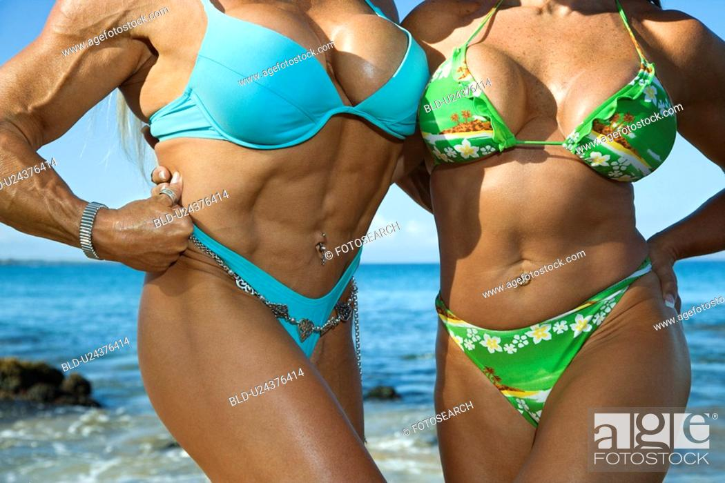 Stock Photo: Women bodybuilders in bikinis on beach.