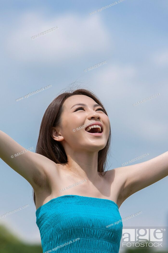 Imagen: Young woman looking up with arms outstretched and smiling happily,.