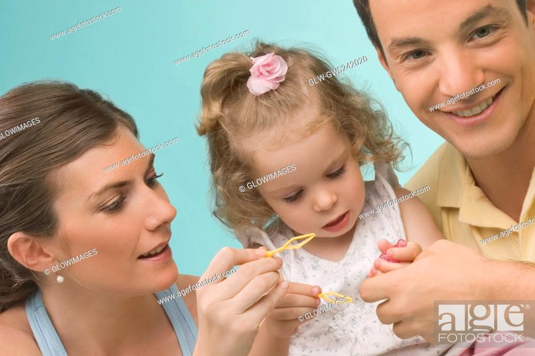 Stock Photo: Close-up of a mid adult couple playing with their daughter.