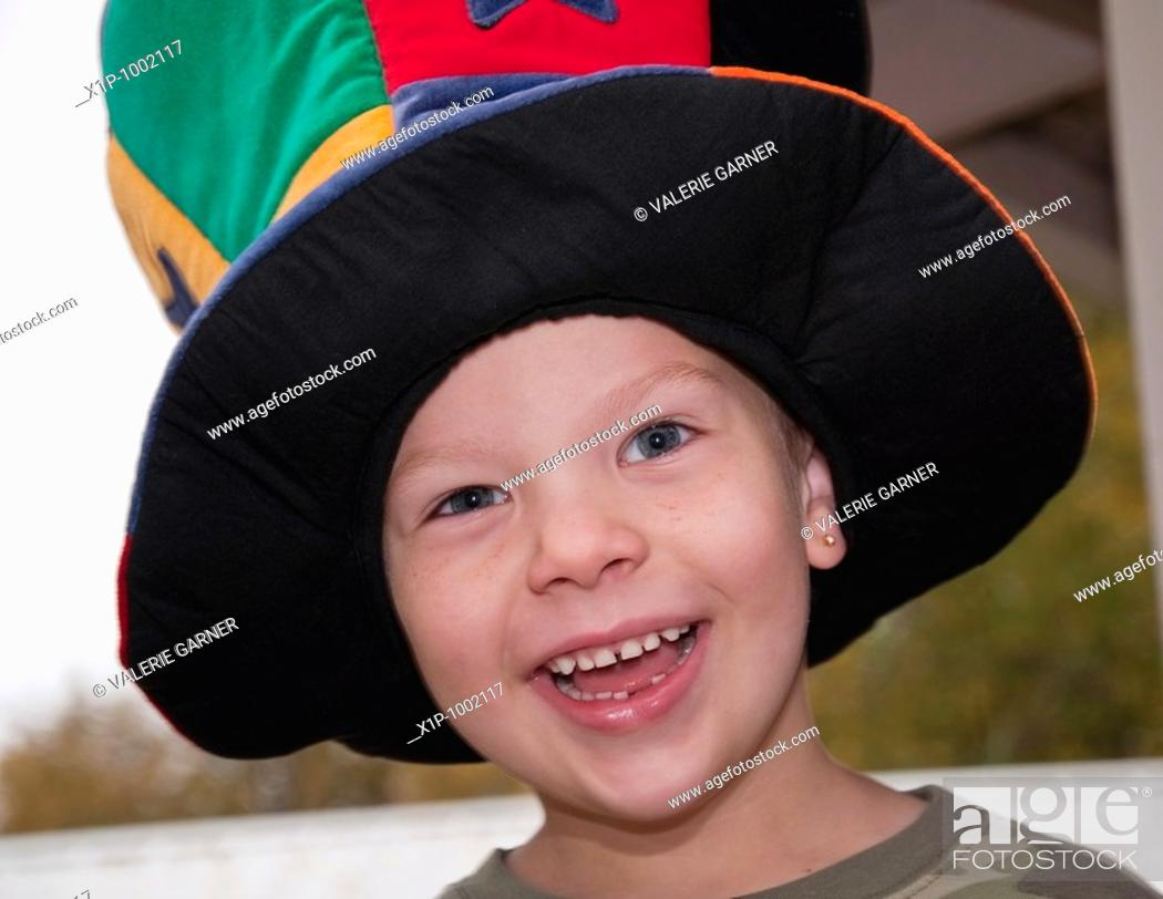 Stock Photo: This cute 4 year old Caucasian boy with freckles and an earring is happy and smiling while wearing a colorful wacky hat Background is intentionally blurred for.