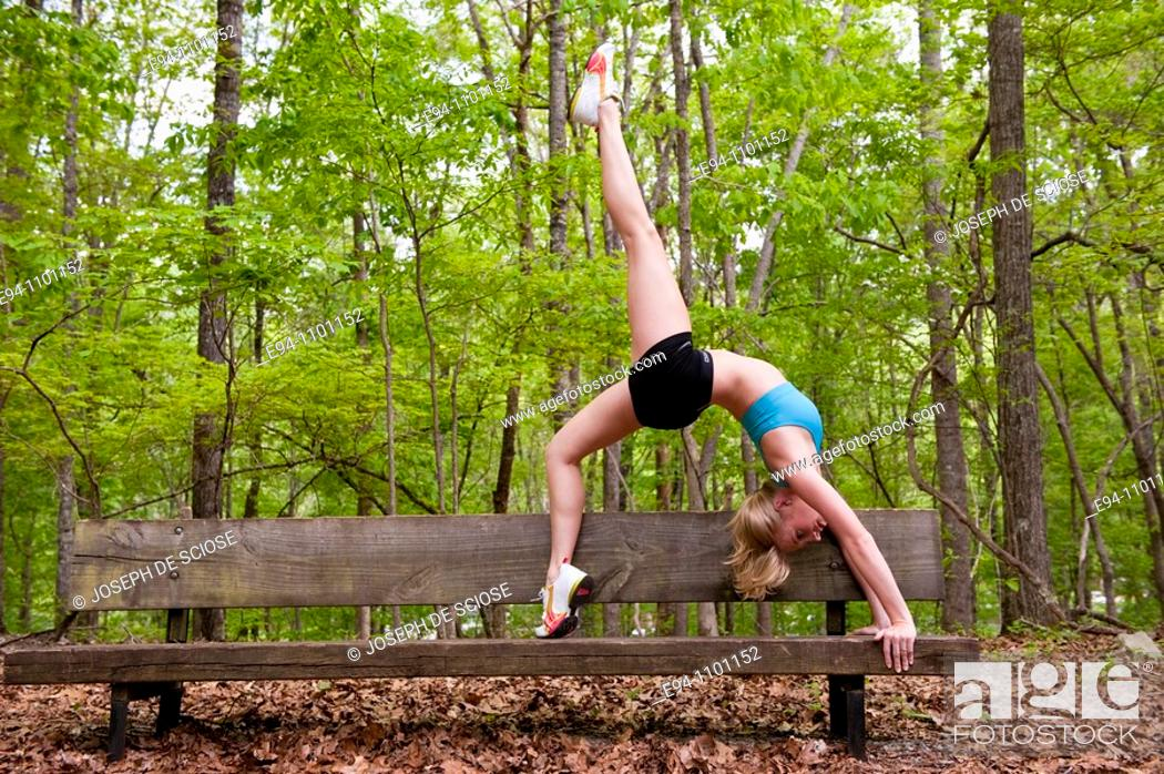 Stock Photo: A young blond woman doing a yoga back bend posture on a wooden bench in a park.