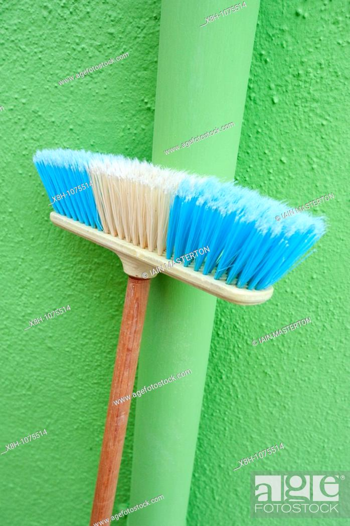 Stock Photo: Household broom leaning against lime green wall of house in Burano island near Venice Italy.