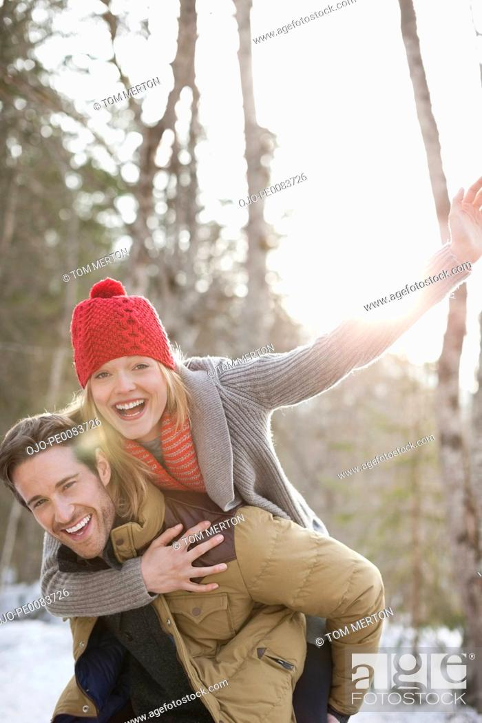 Stock Photo: Portrait of smiling couple piggybacking in snow.