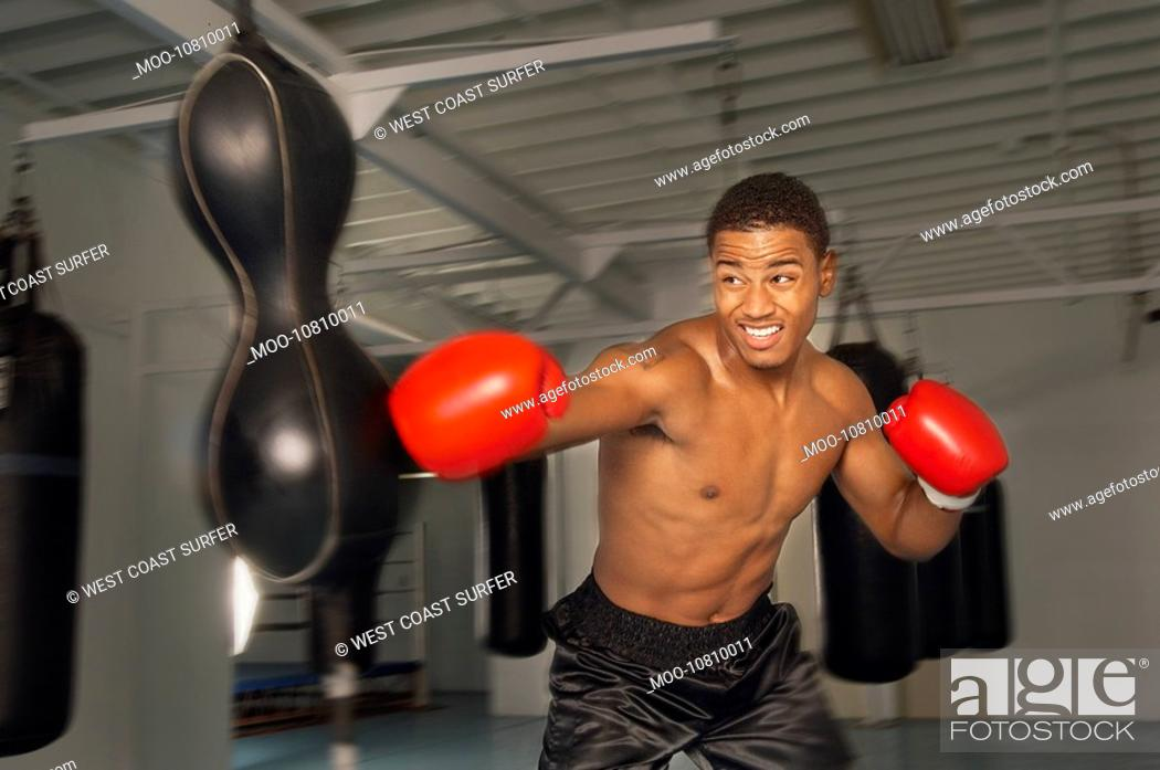 Stock Photo: Boxer hitting punch bag in red gloves in gym.