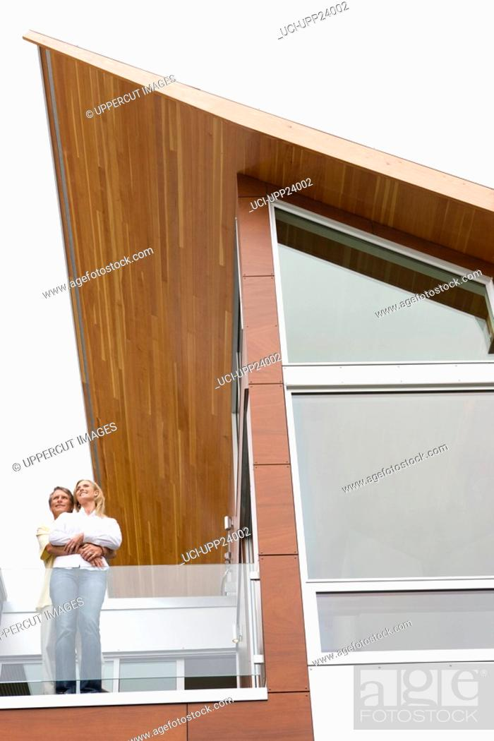 Stock Photo: Couple hugging on balcony of modern house.