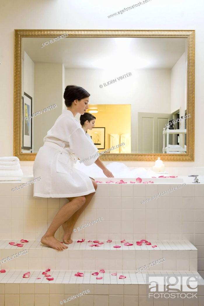 Stock Photo: Woman sitting next to bubble bath.
